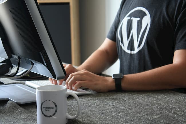 man wearing a wordpress black tshirt working on his computer